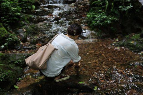 Woman kneeling by stream.