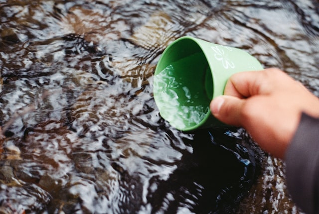 A person dipping water from stream.  Like presentation content, it needs to be filtered.