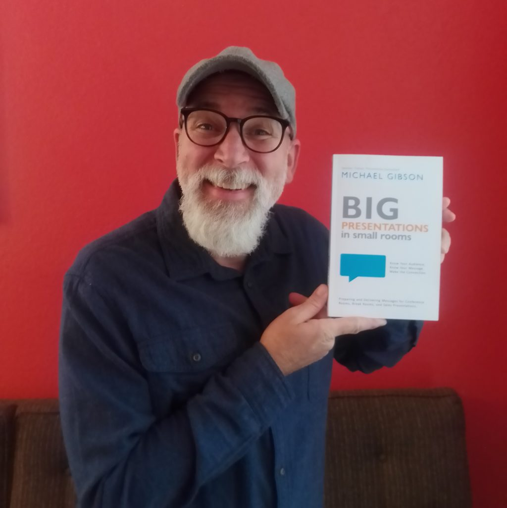Author Mike Gibson holding his book with eye contact in presentation.